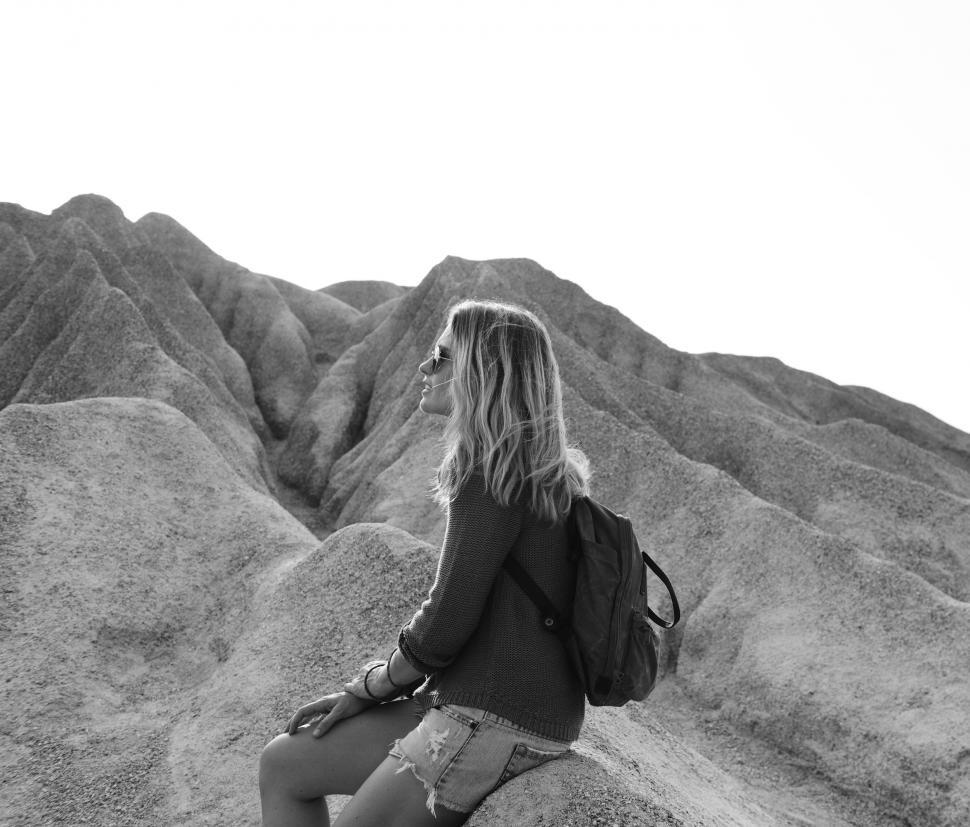 Download Free Stock HD Photo of A young caucasian woman sits on a rock Online