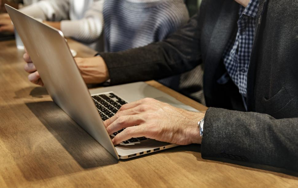 Download Free Stock HD Photo of Sitting at a table, typing on a laptop Online