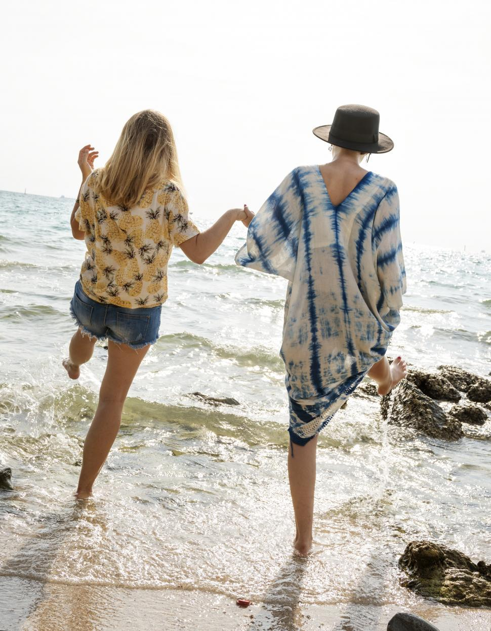 Download Free Stock HD Photo of Rear view of two women splashing seawater with their legs Online
