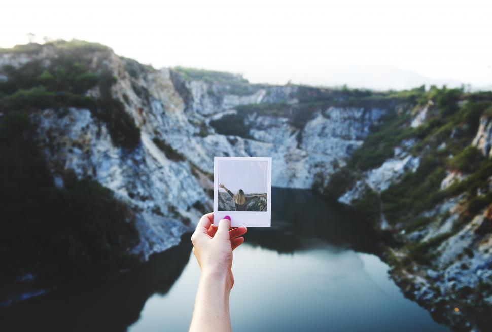 Download Free Stock HD Photo of Hand holding an instant photograph in front of mountains Online