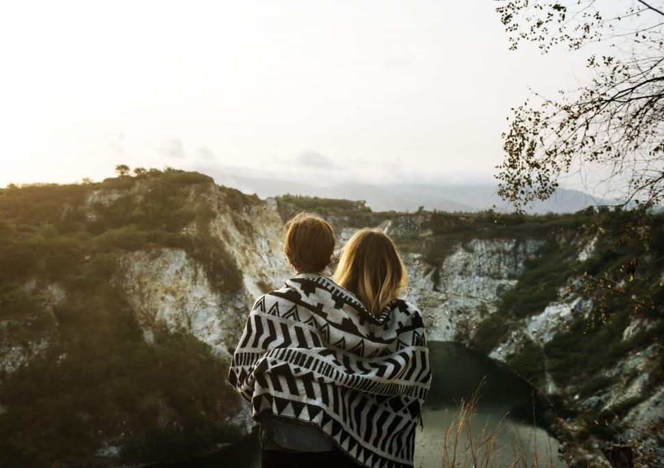 Download Free Stock HD Photo of Back view of two young women wrapped in a blanket looking at mountains Online