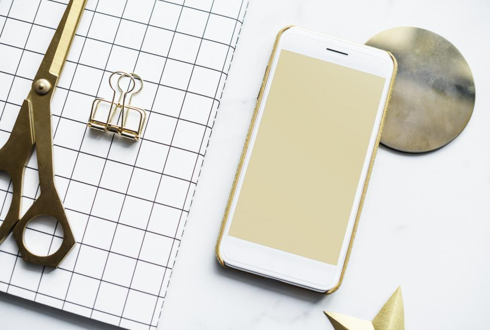 Download Free Stock HD Photo of Flat lay of a mobile phone alongside a notebook and scissors Online