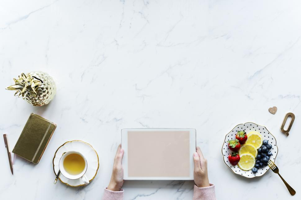 Download Free Stock HD Photo of Overhead view of hands holding a tablet PC over the white marble surface Online