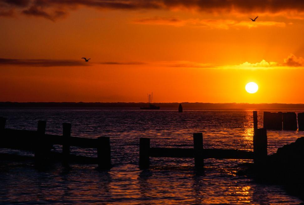 Download Free Stock HD Photo of Setting sun over pilings and ocean Online