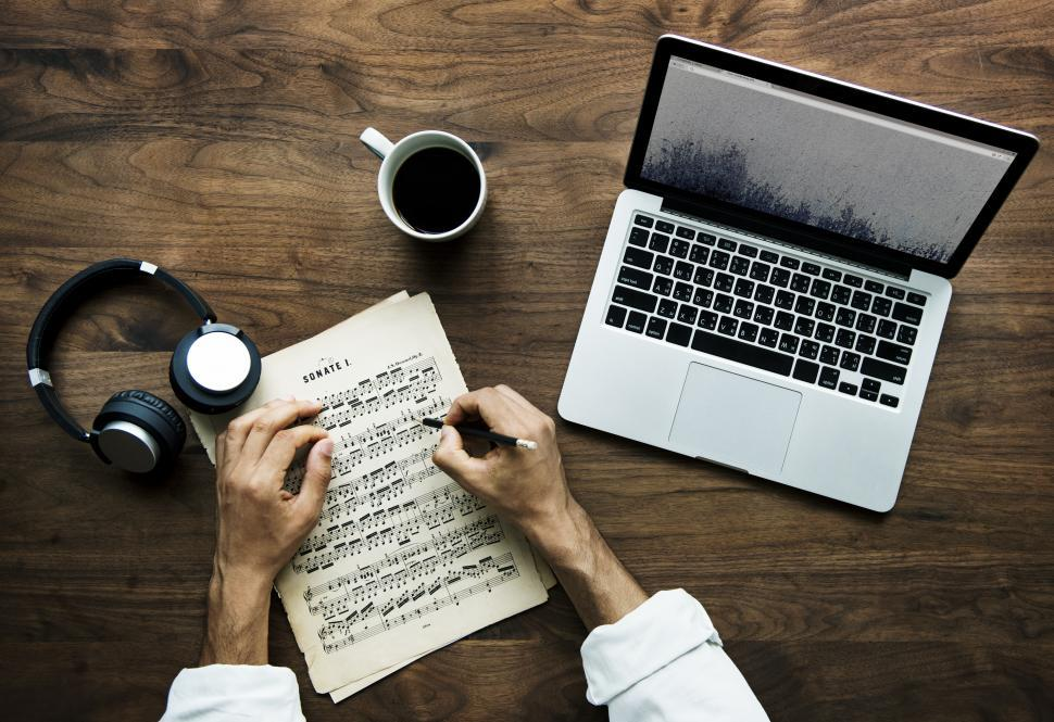Download Free Stock HD Photo of Overhead view of a person s hand writing musical notes on a sheet of paper Online