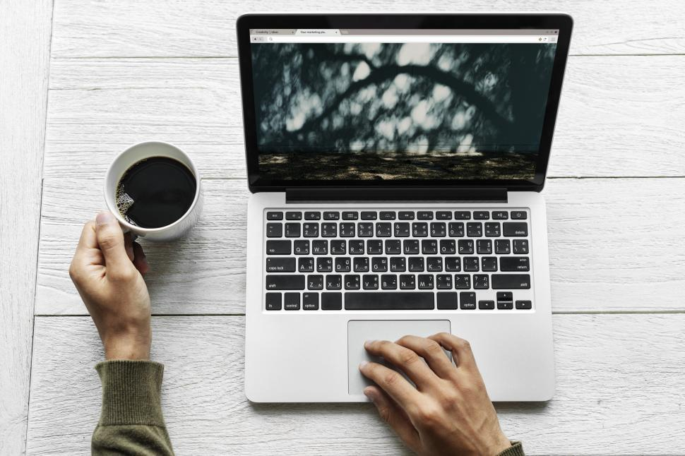 Download Free Stock HD Photo of Overhead view of a hands on laptop with black coffee Online