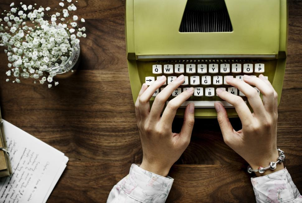 Download Free Stock HD Photo of Overhead view of hands typing on a green vintage typewriter Online