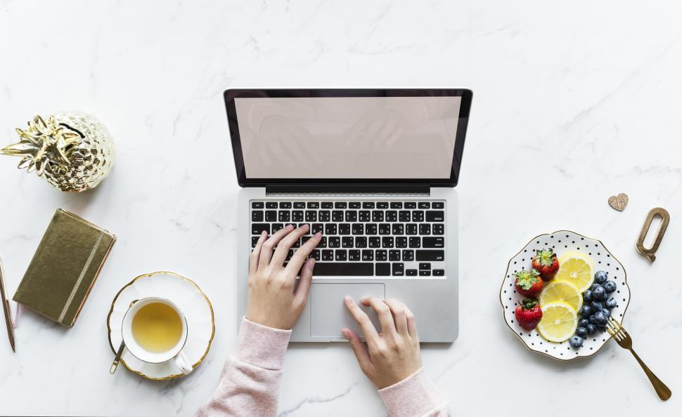 Download Free Stock HD Photo of Hands on a laptop on white marble surface with fruit and coffee Online