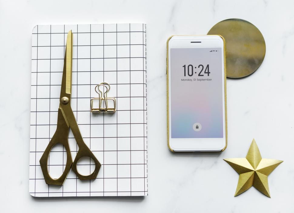 Download Free Stock HD Photo of Flat lay of a mobile phone showing the time alongside a notebook and scissors Online