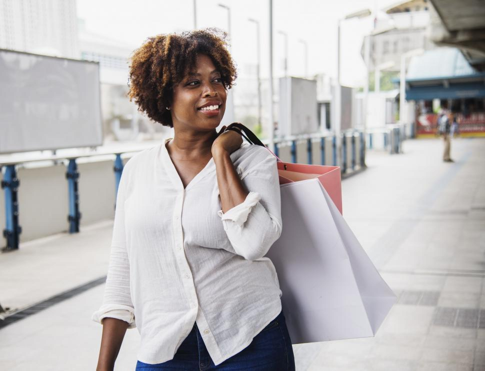 Download Free Stock HD Photo of A young African ethnicity woman carrying shopping bags Online