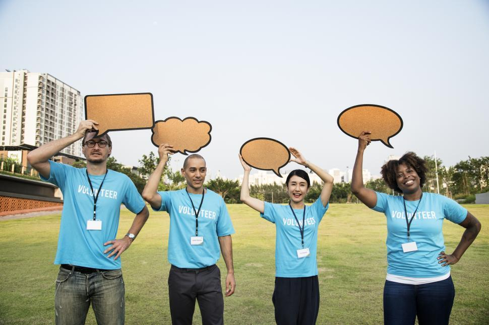 Download Free Stock HD Photo of A group of multiethnicity colleagues raising various cardboard speech bubble cutouts Online