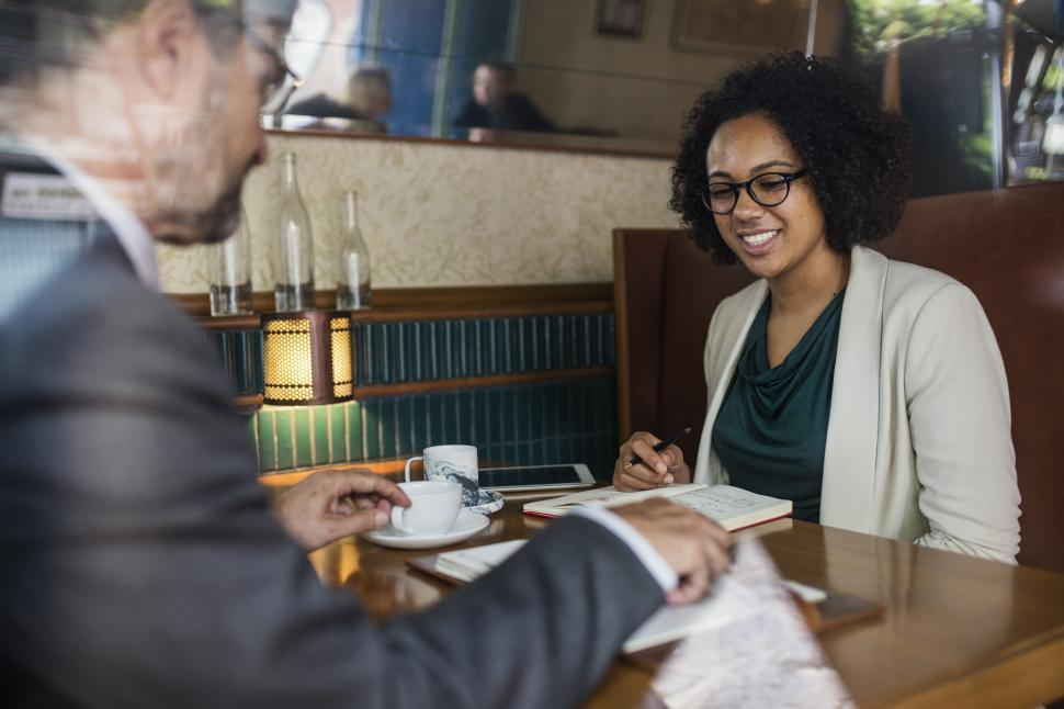 Download Free Stock HD Photo of A senior man and a young female colleague at a cafe Online