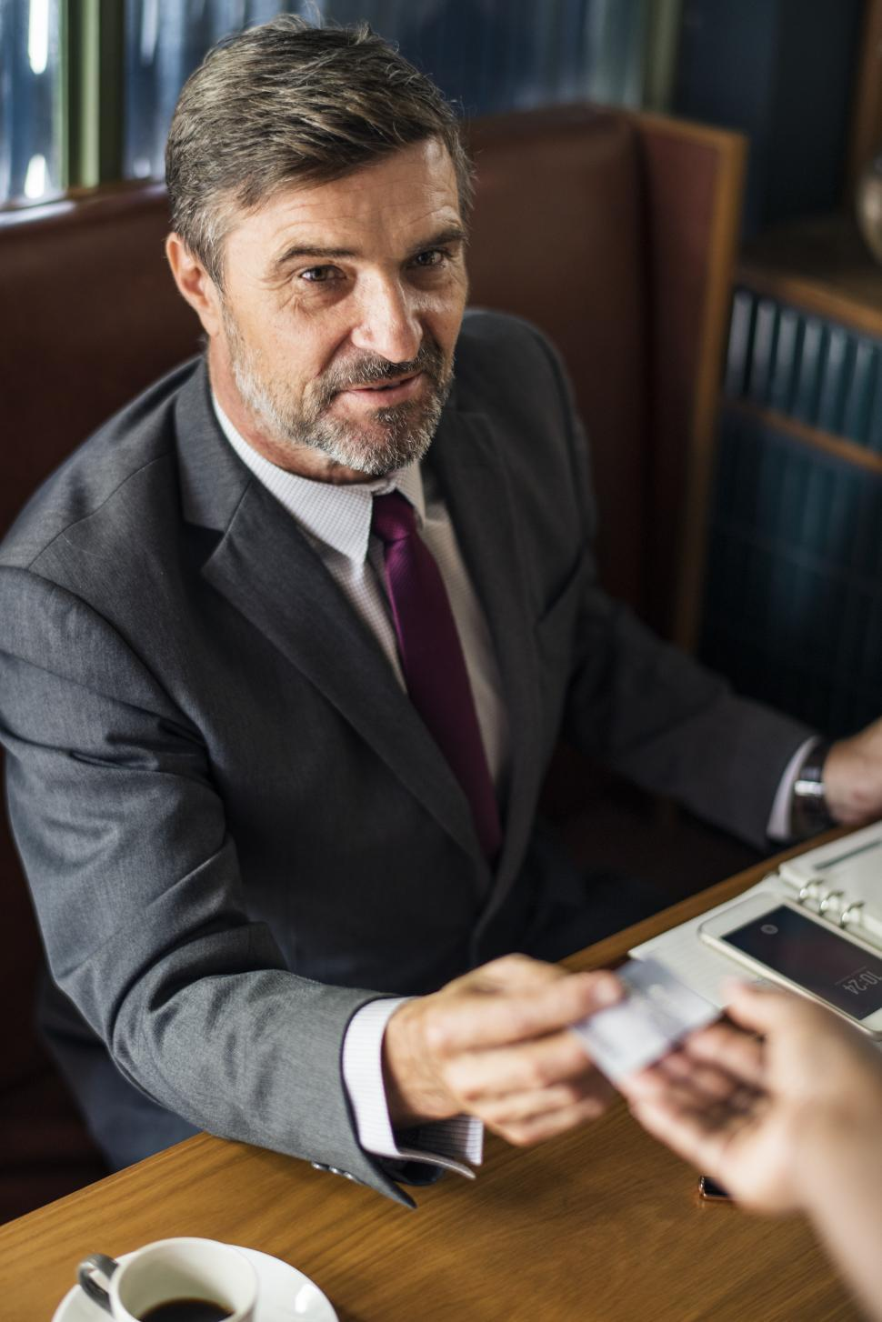 Download Free Stock HD Photo of A mature business man paying with his card at a cafe Online