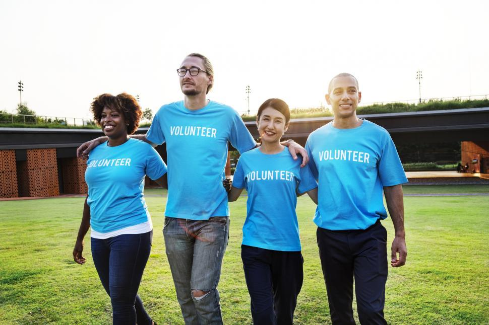 Download Free Stock HD Photo of A group of multiethnic volunteers walking together on the grass Online