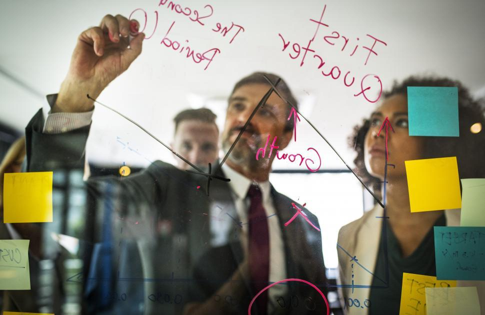Download Free Stock HD Photo of A bearded Caucasian businessman drawing a graph on the glass panel Online