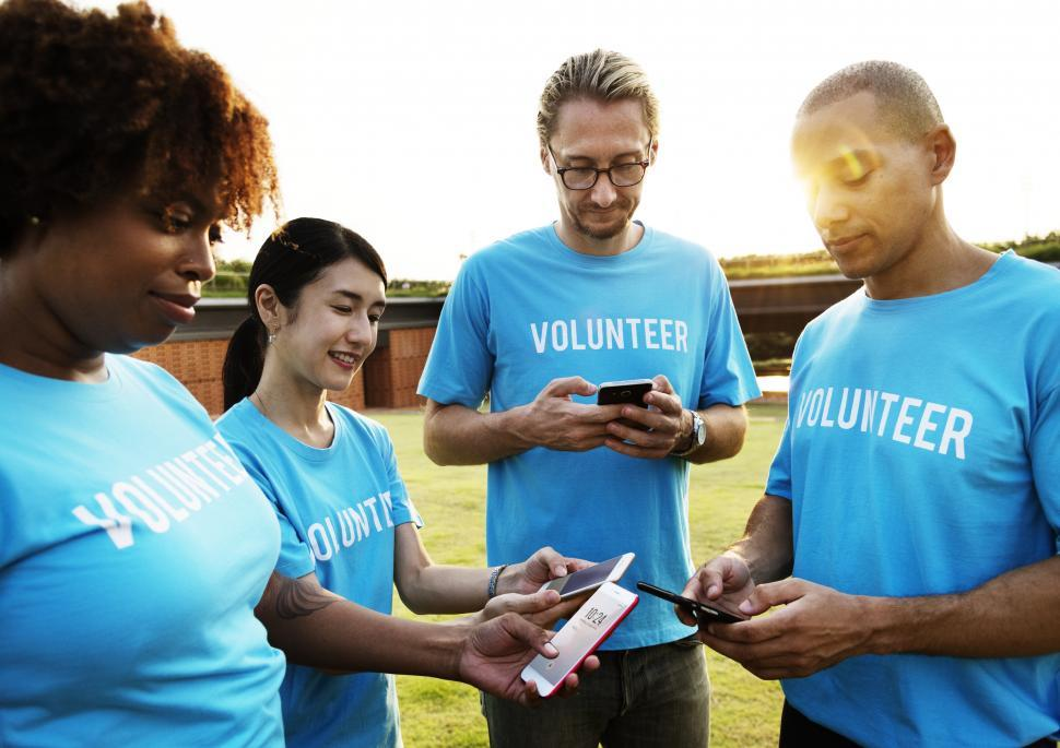 Download Free Stock HD Photo of A group of multiethnic volunteers looking at their mobile phones Online