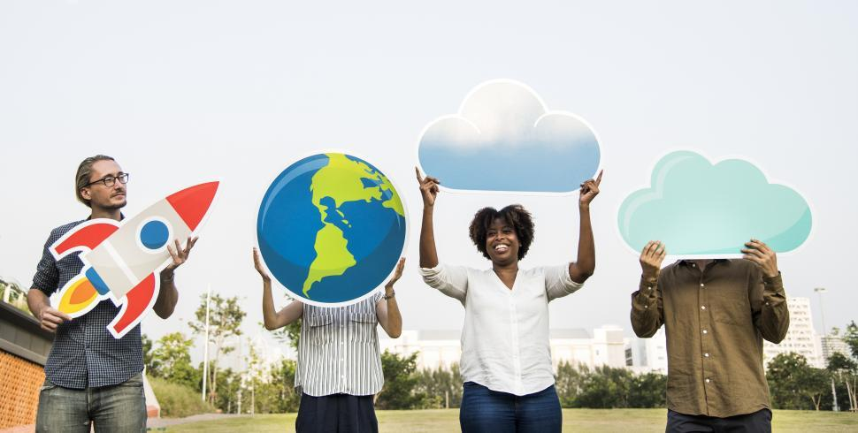 Download Free Stock HD Photo of A group of people posing with a globe, a rocket and cloud shaped cardboard cutouts Online