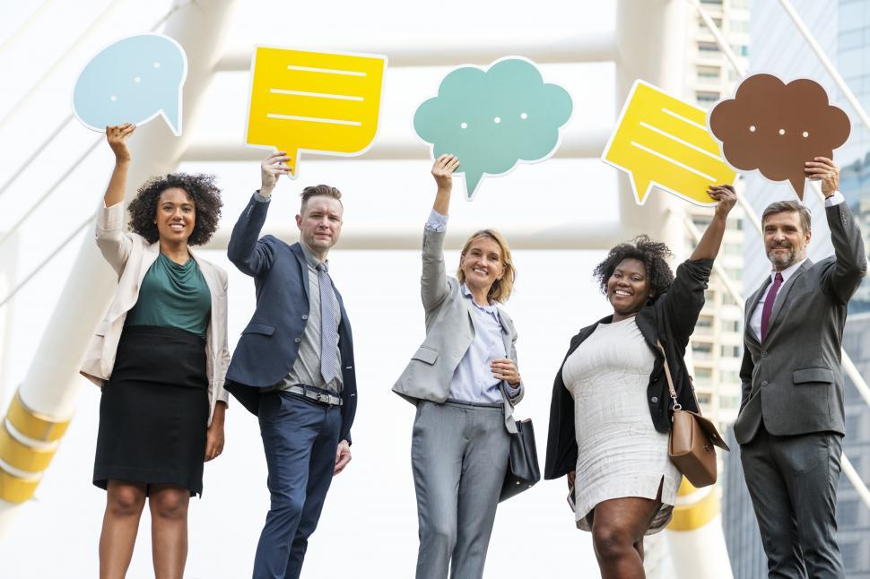 Download Free Stock HD Photo of A group of colleagues raising shaped speech bubble cutouts Online