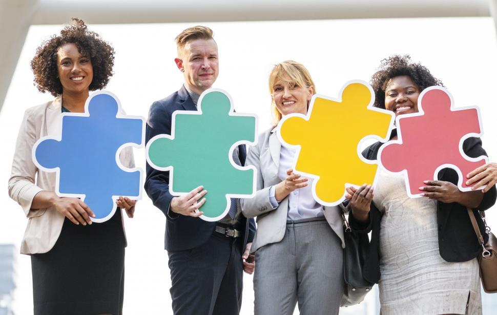 Download Free Stock HD Photo of A group of coworkers holding cardboard jigsaw puzzle cutouts Online