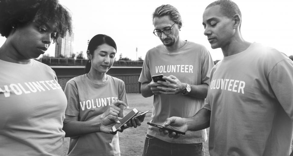 Download Free Stock HD Photo of Black and white photo of volunteers looking at their mobile phones Online
