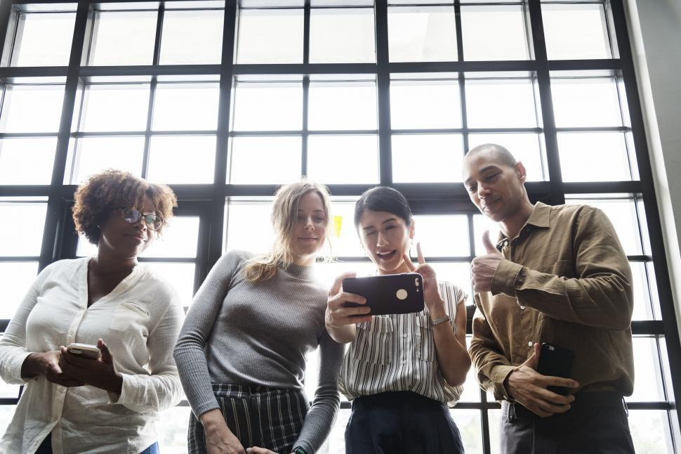 Download Free Stock HD Photo of Multiethnic colleagues looking at a mobile devices Online