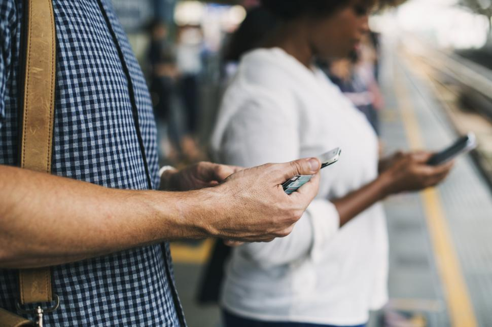 Download Free Stock HD Photo of Close up of commuters looking at their mobile phones Online