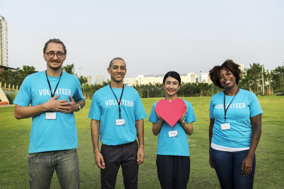 Download Free Stock HD Photo of A group of volunteers posing with a heart shaped cardboard cutout Online