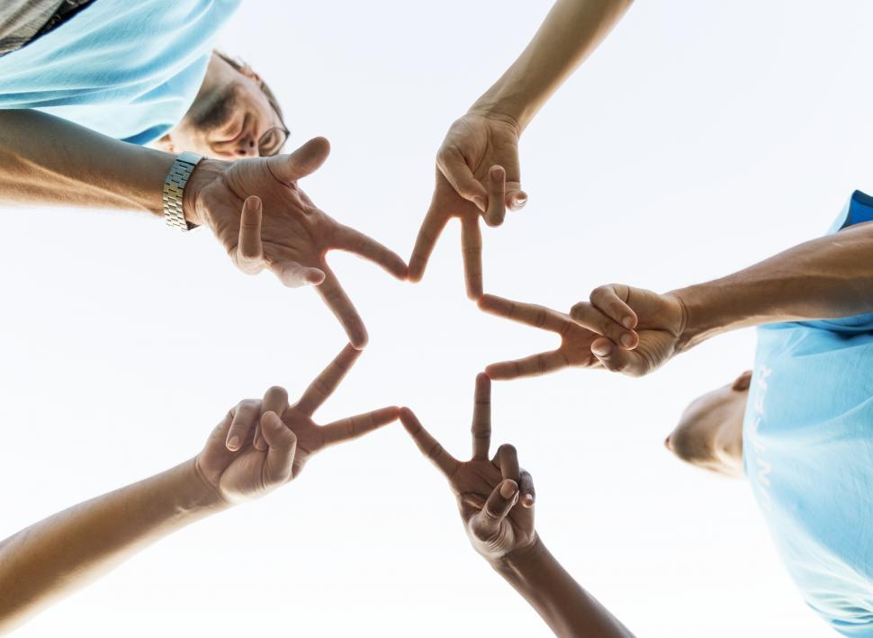 Download Free Stock HD Photo of Low angle view looking up at volunteers forming a star with fingers Online