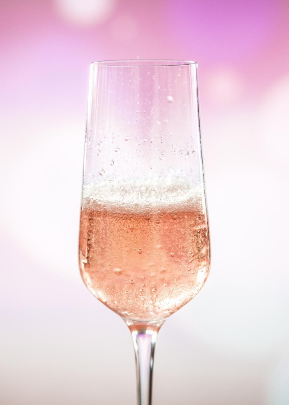 Download Free Stock HD Photo of Close up of a champagne glass with pink and white background Online