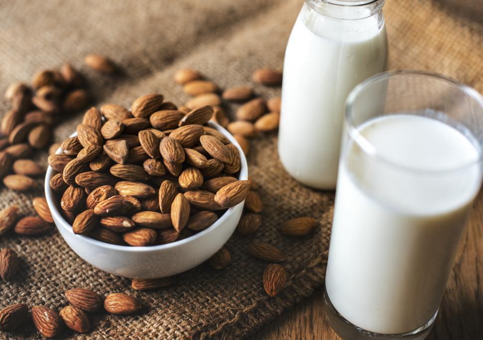 Download Free Stock HD Photo of A bowl full of almonds and a glass and bottle of milk Online