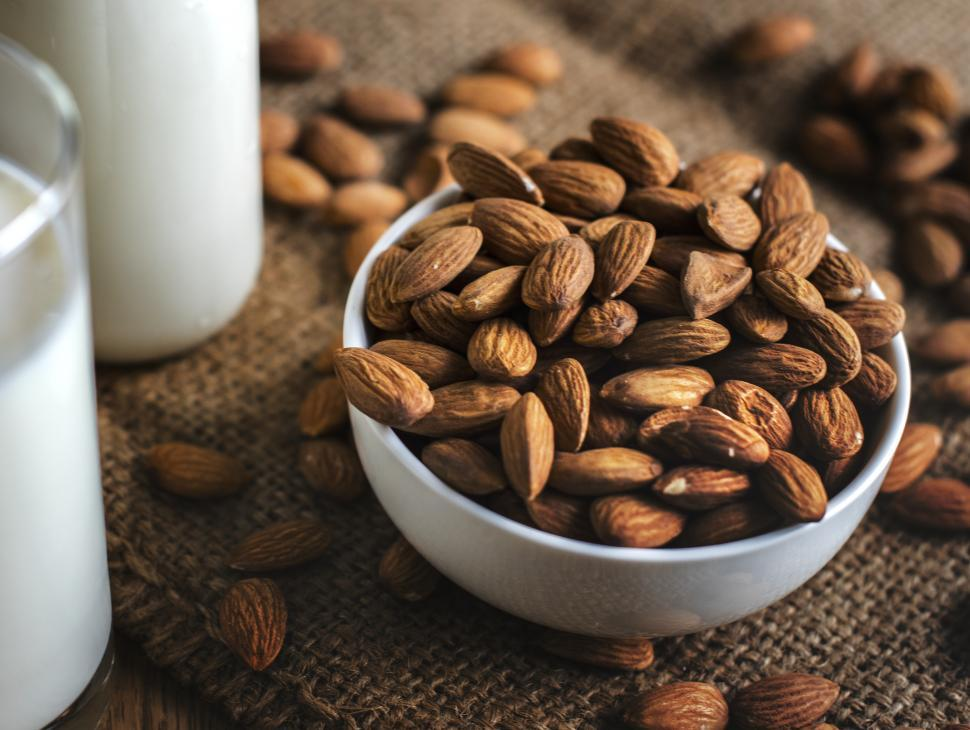 Download Free Stock HD Photo of Close up of almonds alongside a glass of milk Online