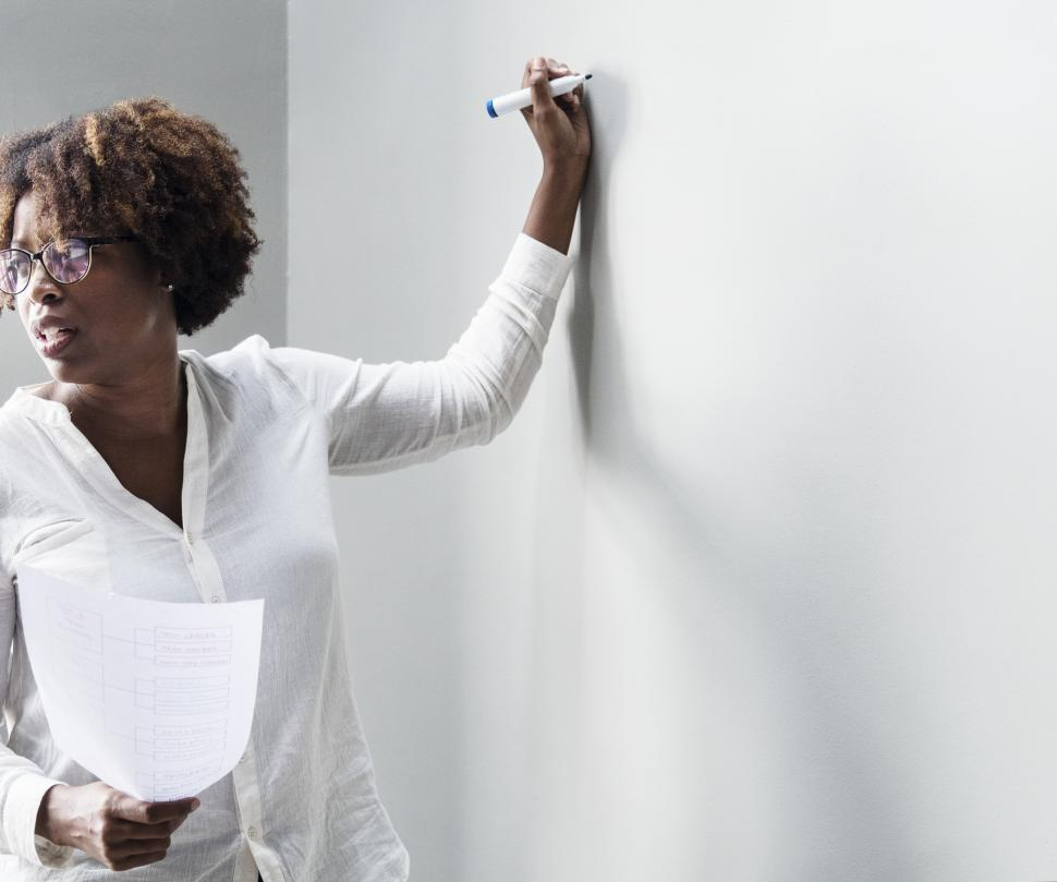 Download Free Stock HD Photo of An woman writing on the board, looking at audience Online
