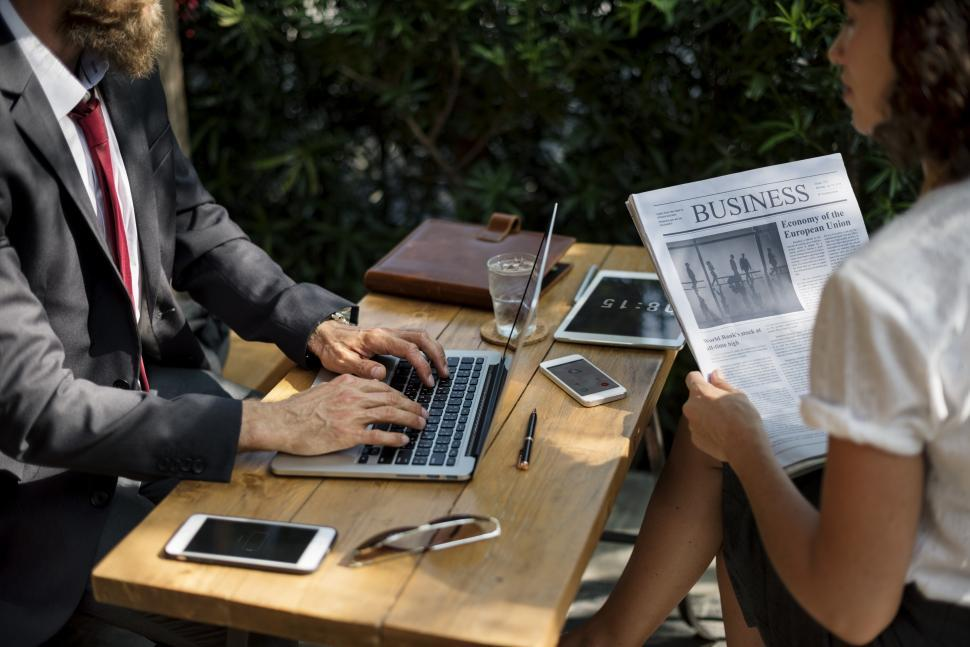 Download Free Stock HD Photo of Close up of two business people talking over news of the day Online