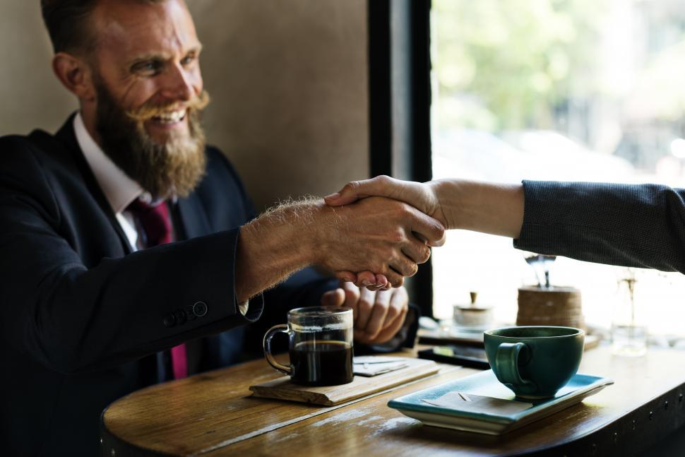Download Free Stock HD Photo of Bearded man shaking hands at a table Online