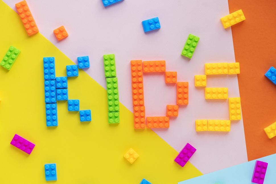 Download Free Stock HD Photo of Flat lay of the text KIDS written with plastic toy bricks Online