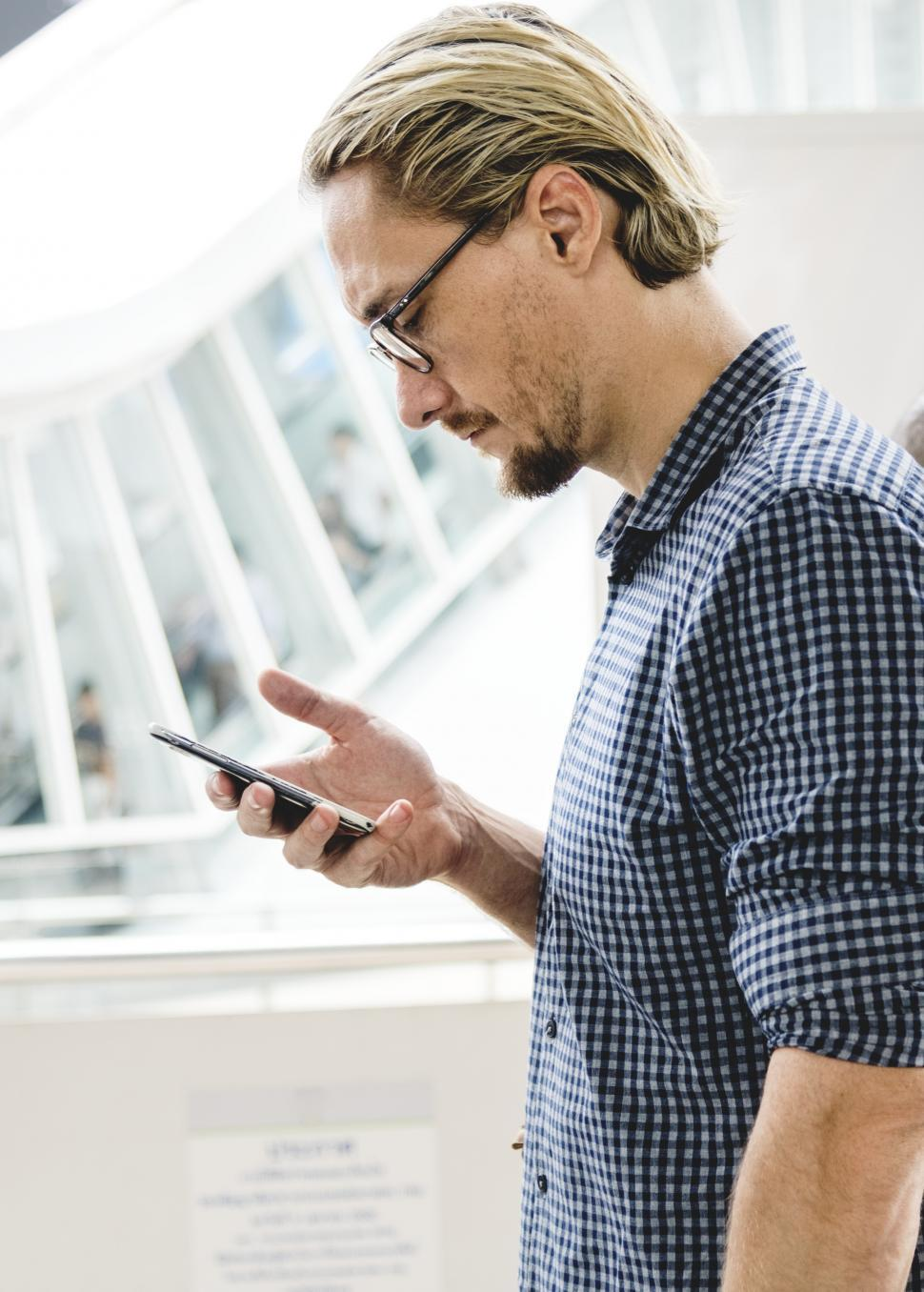 Download Free Stock HD Photo of A bearded Caucasian man looking at his mobile phone Online