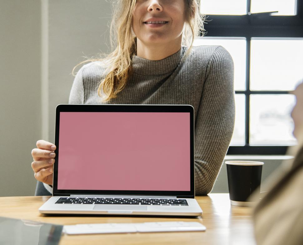 Download Free Stock HD Photo of A young Caucasian woman showig a laptop - blanks screen Online