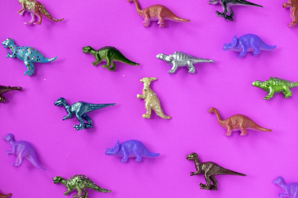 Download Free Stock HD Photo of Colorful toy dinosaurs on magenta surface Online