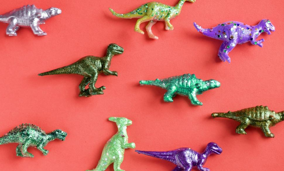 Download Free Stock HD Photo of Colorful toy dinosaurs on red surface Online