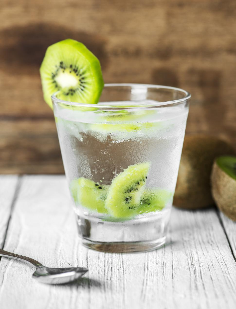 Download Free Stock HD Photo of Close up of a clear glass of beverage garnished with kiwi slices Online