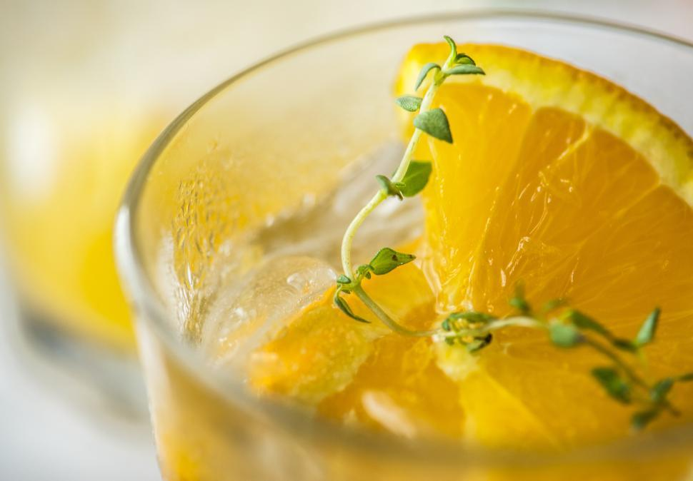 Download Free Stock HD Photo of Close up of chilled beverage in a glass garnished with orange slices Online