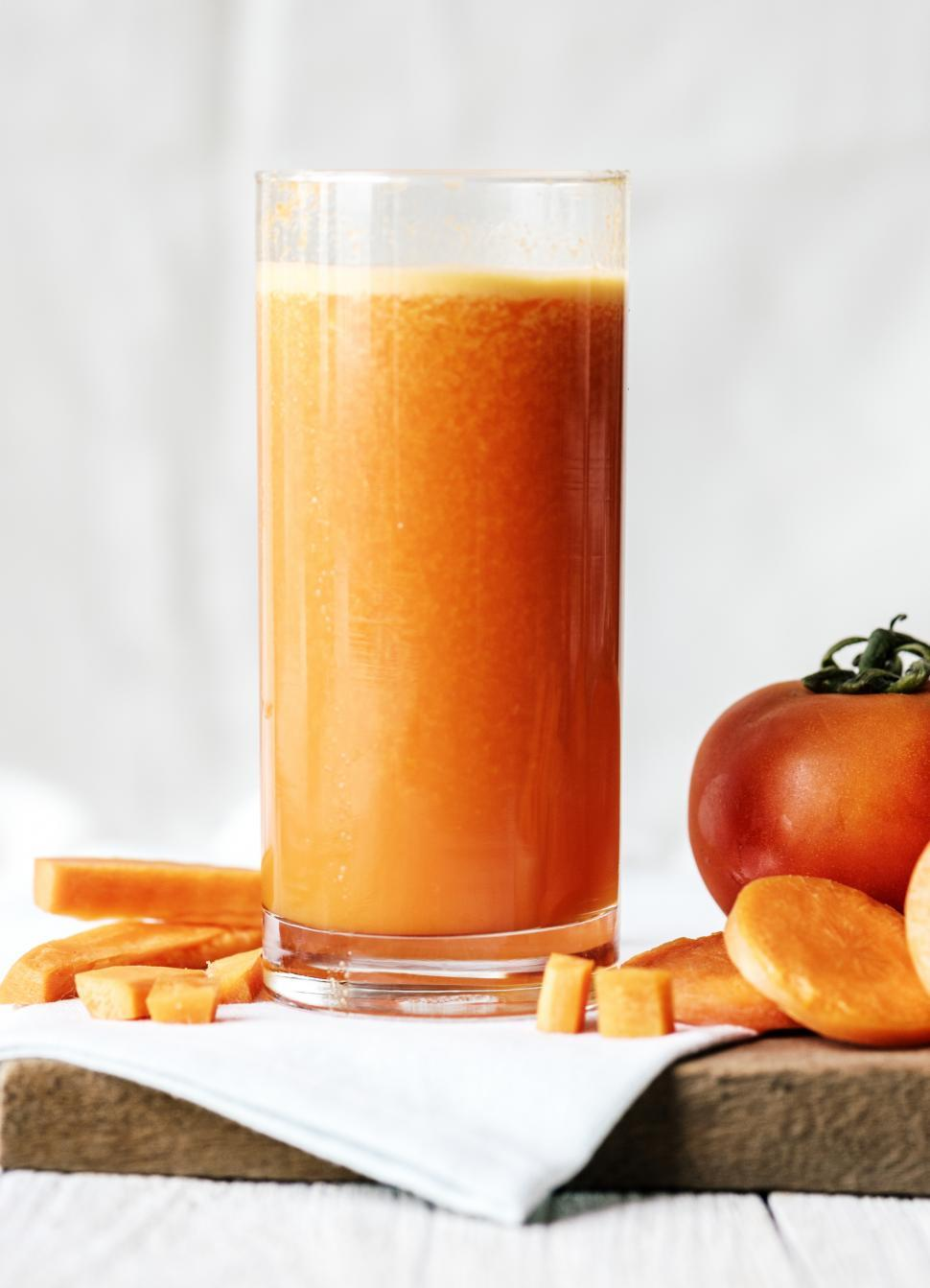 Download Free Stock HD Photo of Close up of carrot and tomato smoothie served in a glass Online