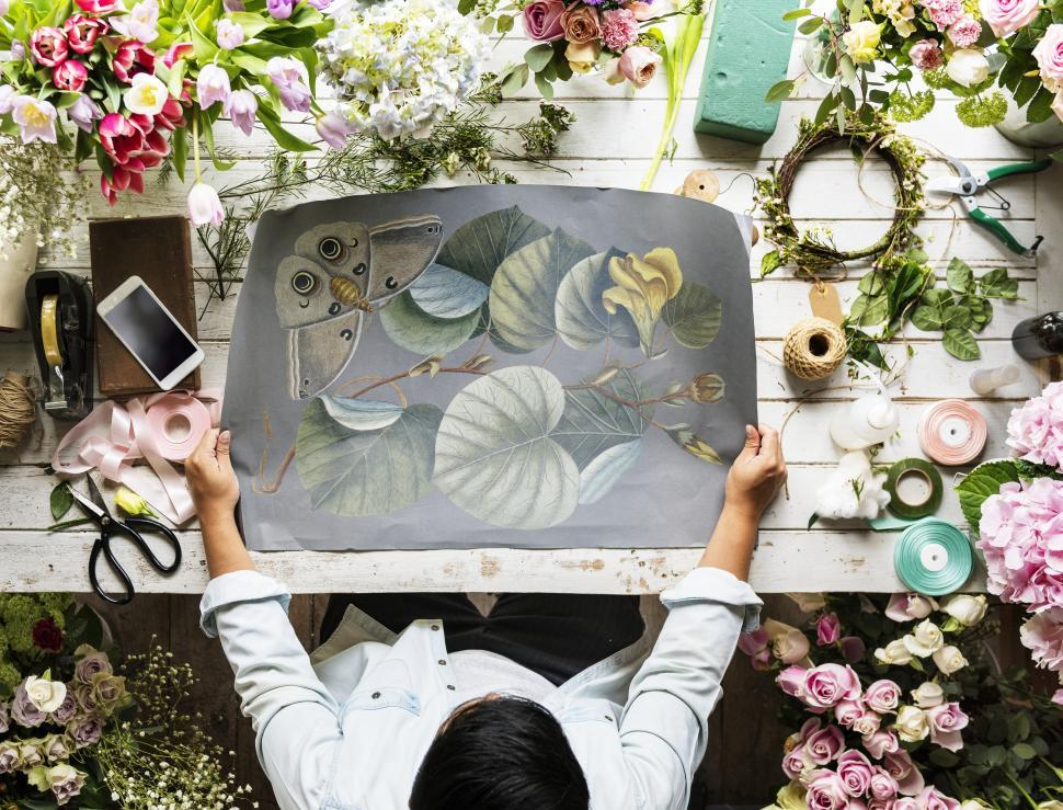Download Free Stock HD Photo of Flat lay of a florist looking at illustration on paper Online