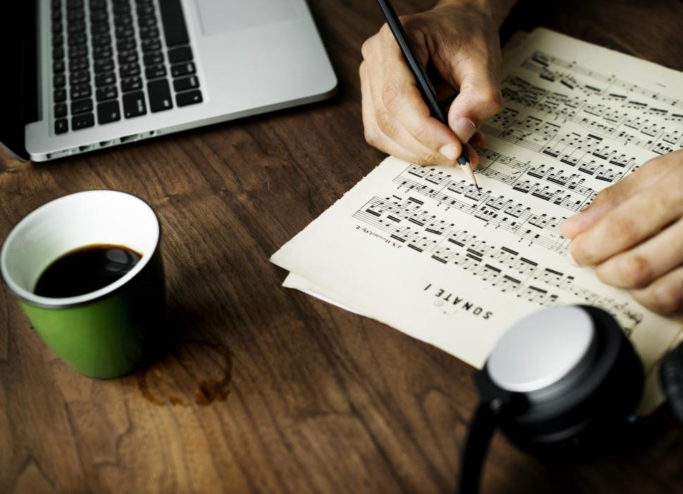 Download Free Stock HD Photo of Close up of a person writing musical notes on a sheet of paper Online