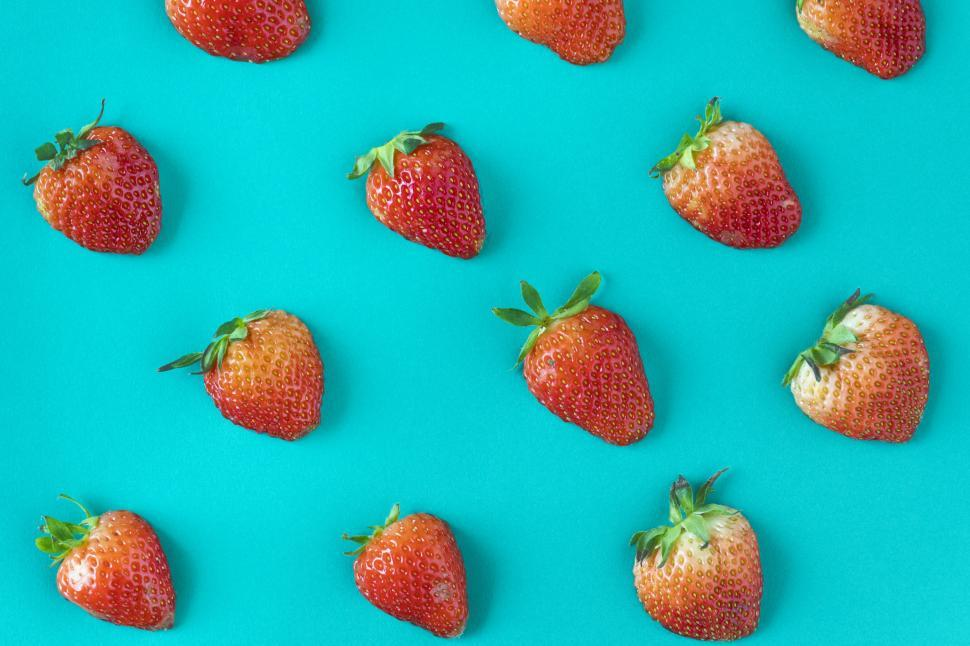 Download Free Stock HD Photo of Flay lay of strawberries on greenish blue surface Online