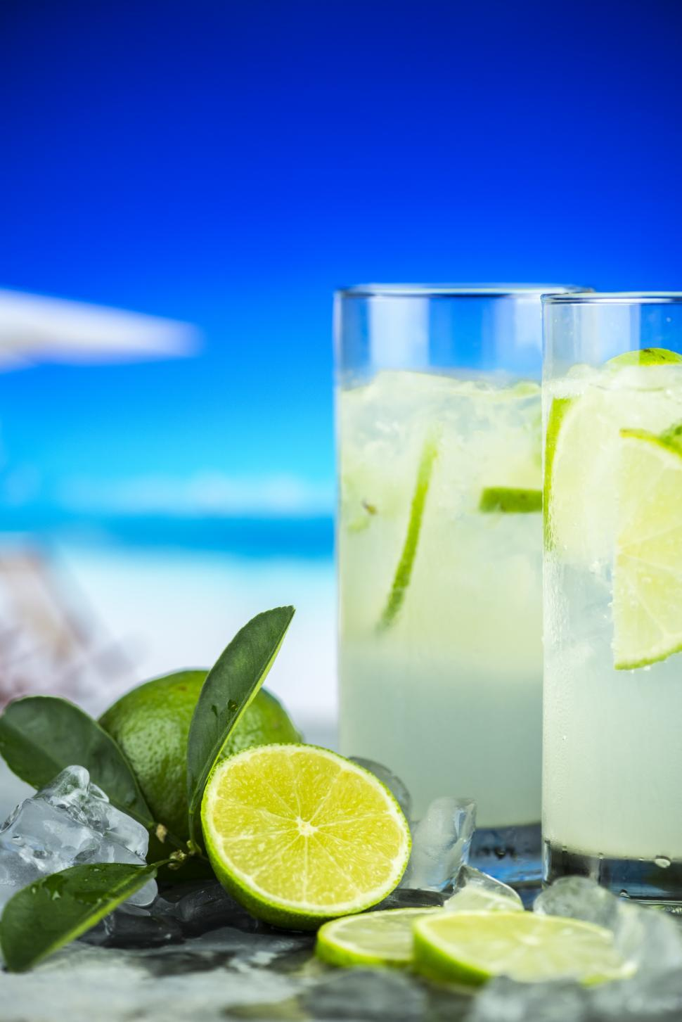 Download Free Stock HD Photo of Close up of two glasses full of chilled mojito, beach scene  Online
