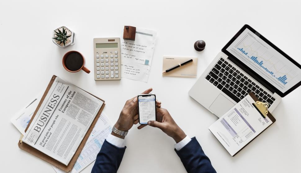 Download Free Stock HD Photo of Overhead view of a operating a mobile phone surrounded with a laptop, a coffee mug along with other items on the office table Online