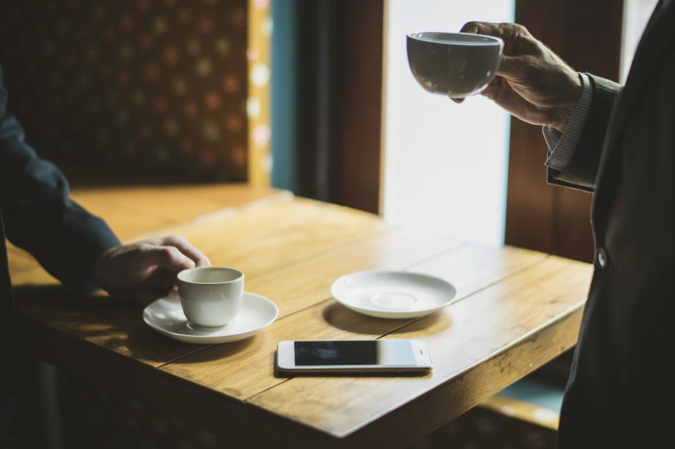Download Free Stock HD Photo of Two anonymous people drinking coffee at a cafe Online