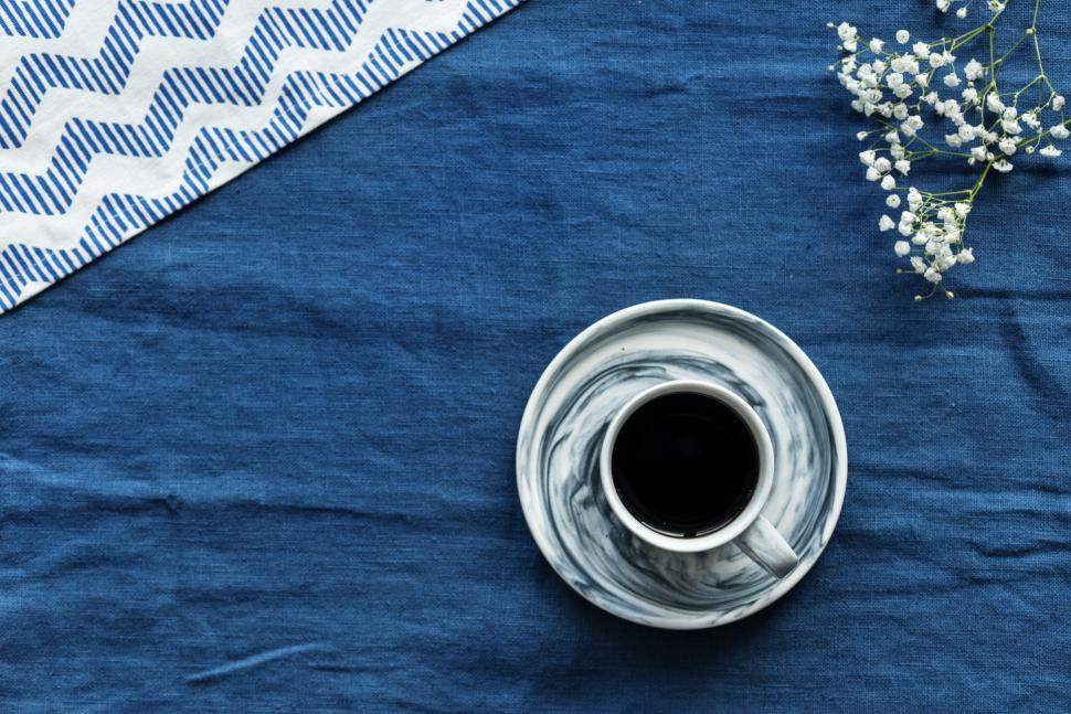 Download Free Stock HD Photo of Flat lay of a cup of coffee on blue background Online