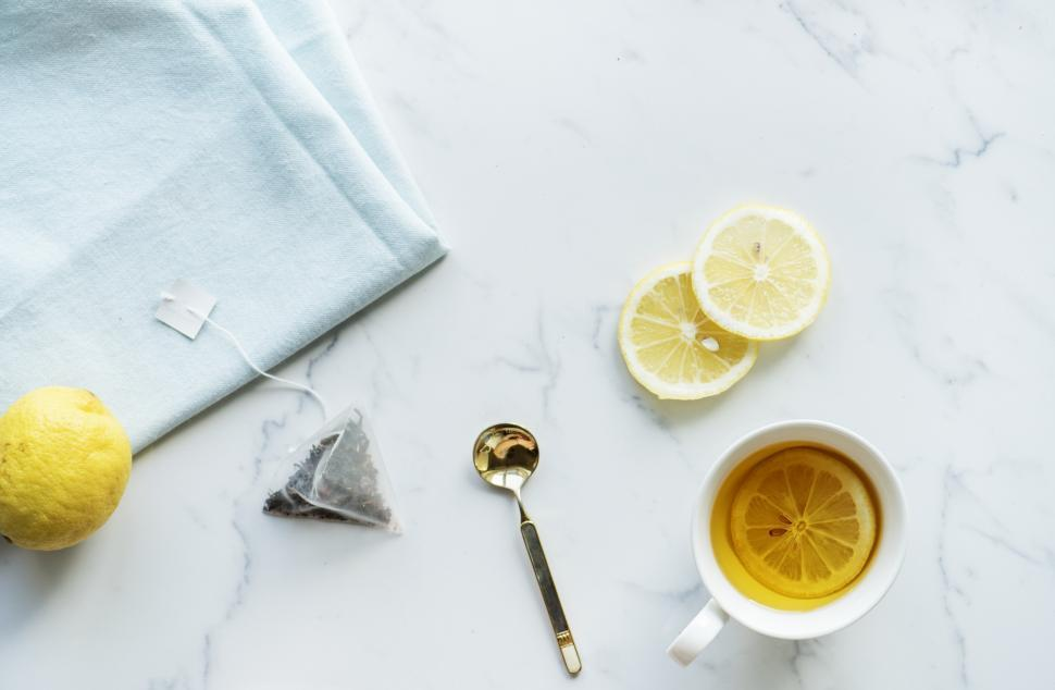 Download Free Stock HD Photo of Flat lay of a cup of lemon tea on the marble surface with citrus Online